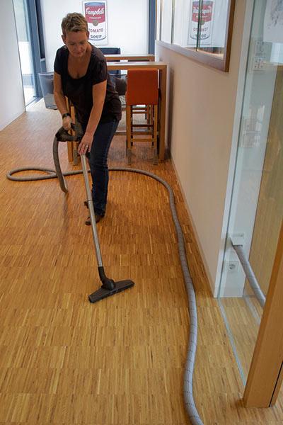 Frau saugt Staub auf dem Fußboden