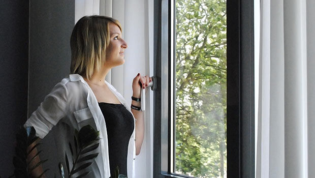 Junge Frau am Fenster, manuelle Wohnraumlüftung