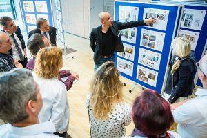 Hanns-Christian Hofmann, Innenarchitekt und Jurymitglied, erläutert dem Fachpublikum die Wettbewerbsbeiträge.